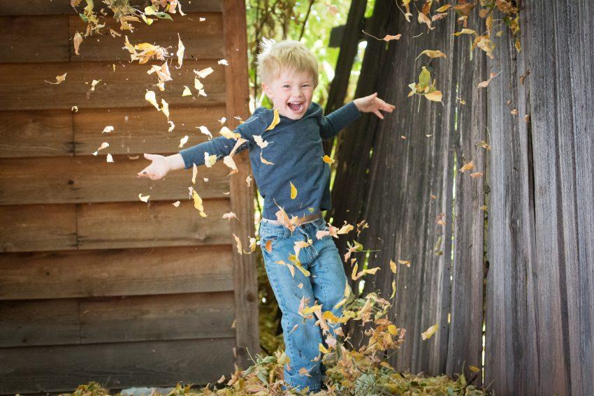 Laps sügiseste lehtedega mängimas